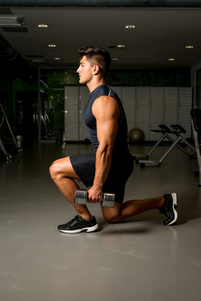 performing a dumbbell lunge in your garage gym
