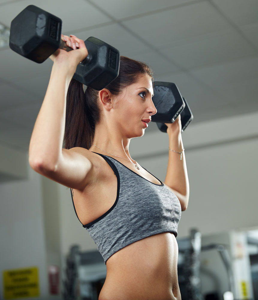 performing a dumbbell shoulder press in a garage gym