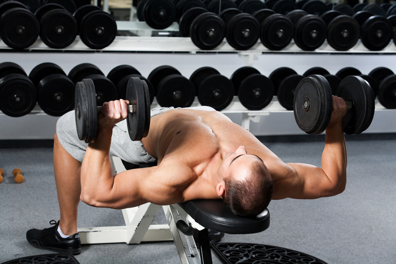 man doing dumbbell bench press on a portable foldable bench