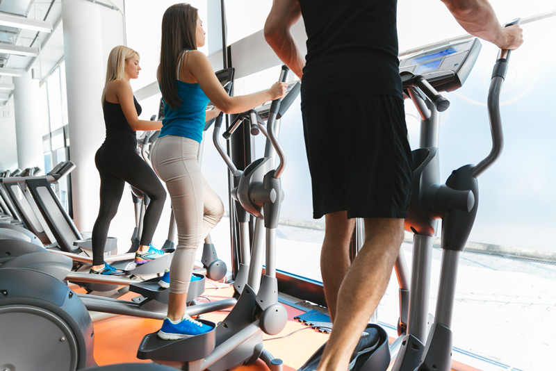 group working out on a series of compact elliptical machines