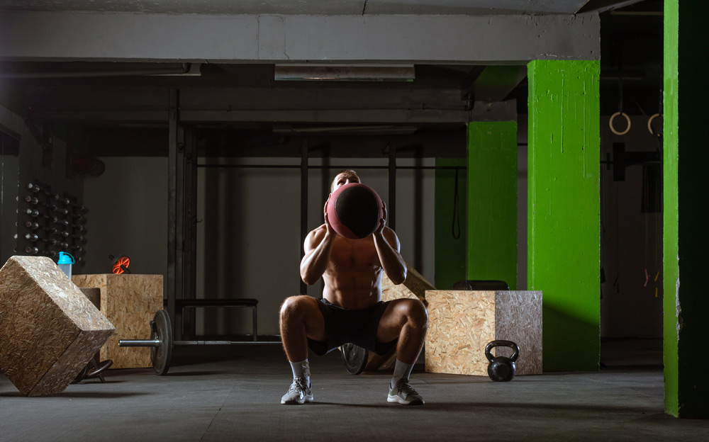 doing air squats with a medicine slam ball