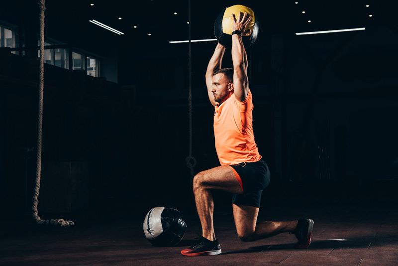 doing an overhead lunge with a medicine ball slam