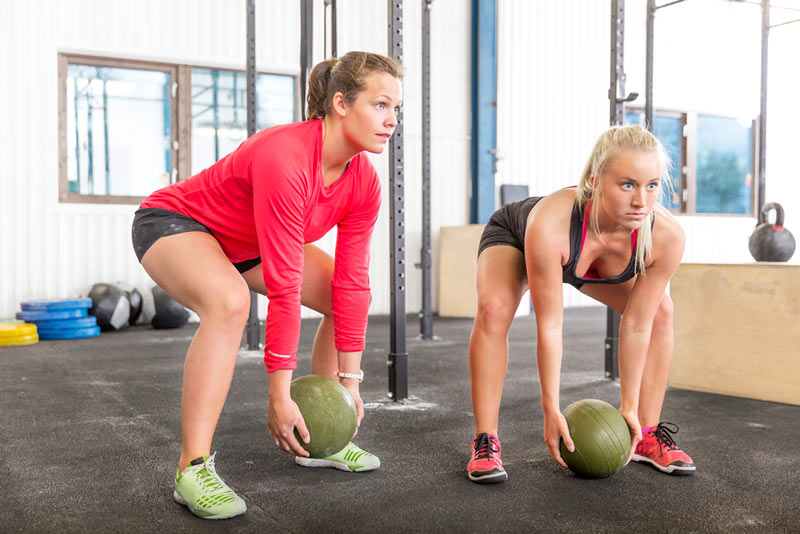 two girls working out with a slam ball at the gym